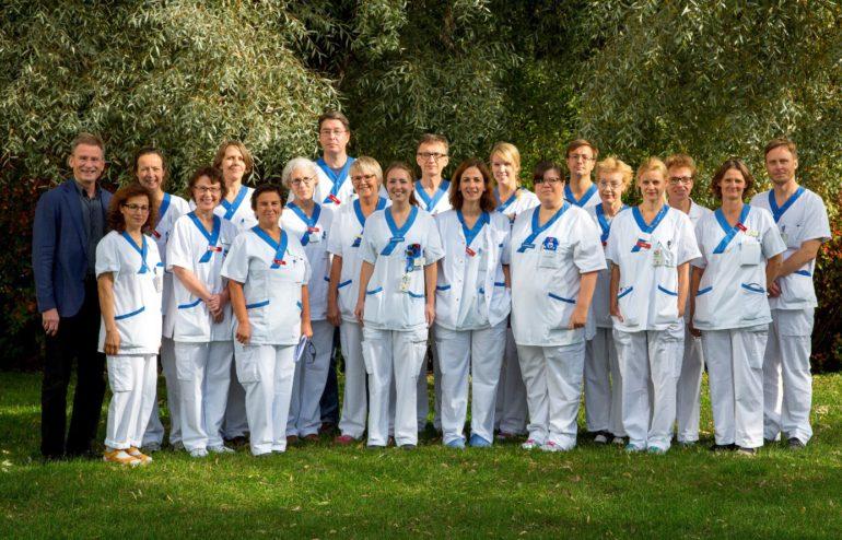 Glada medarbetare på reumatologen Uppsala, placerade framför parkens pilträd (Salix)